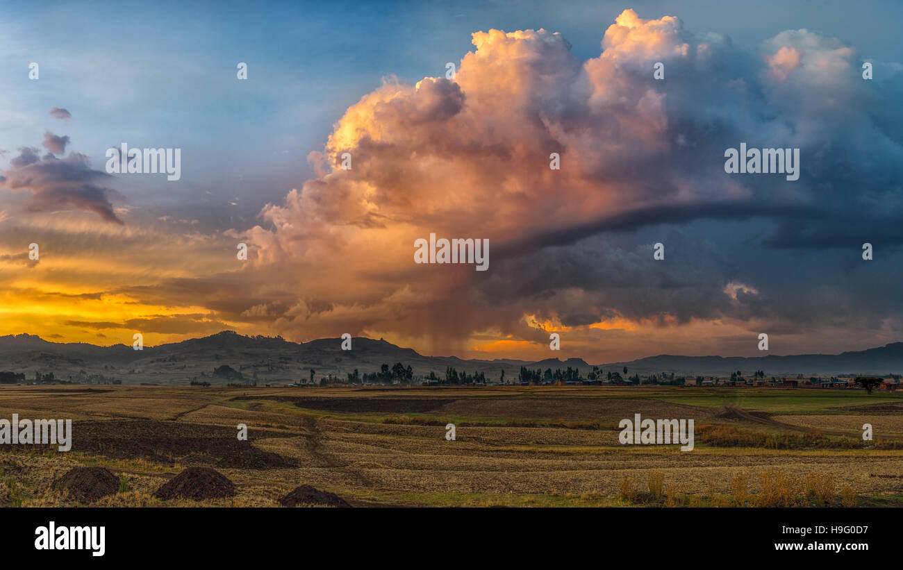 A rural lanscape with stormy clouds emerging out of the mountains during sunset near the town of Legetafo just outside - Stock Image