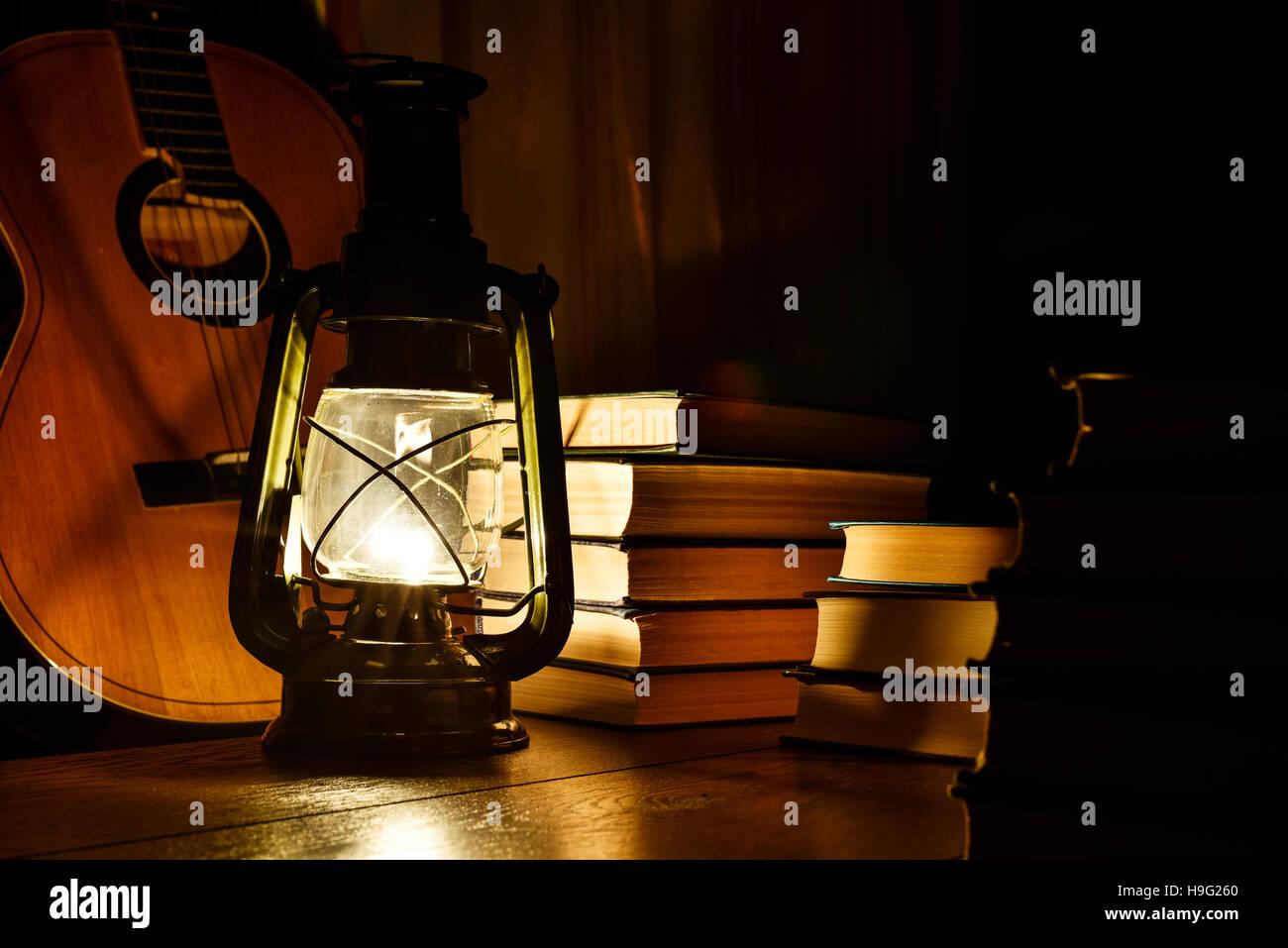 Kerosene lamp, guitar and books on the table - Stock Image