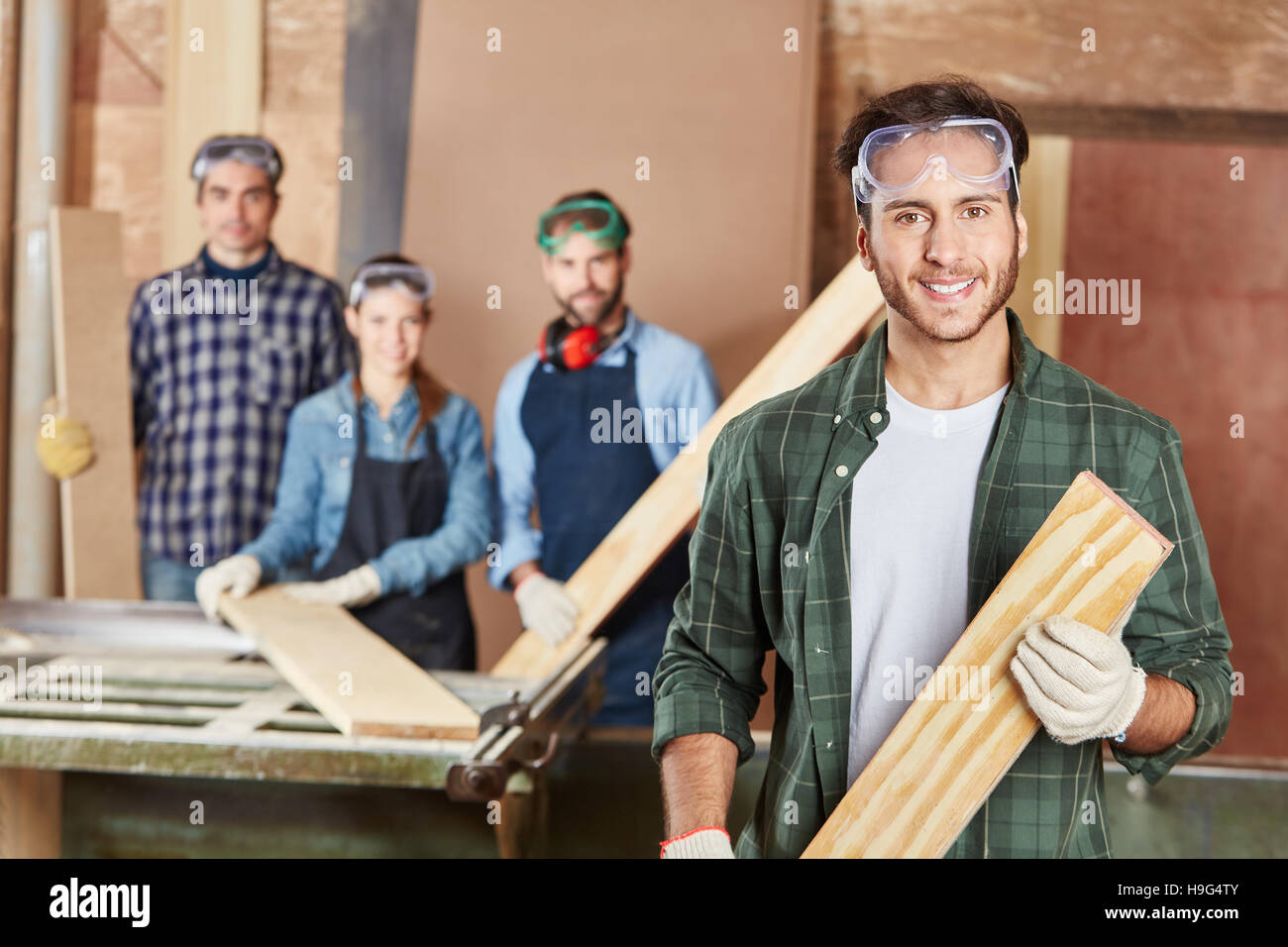 Man as carpenter with wood on his hands - Stock Image