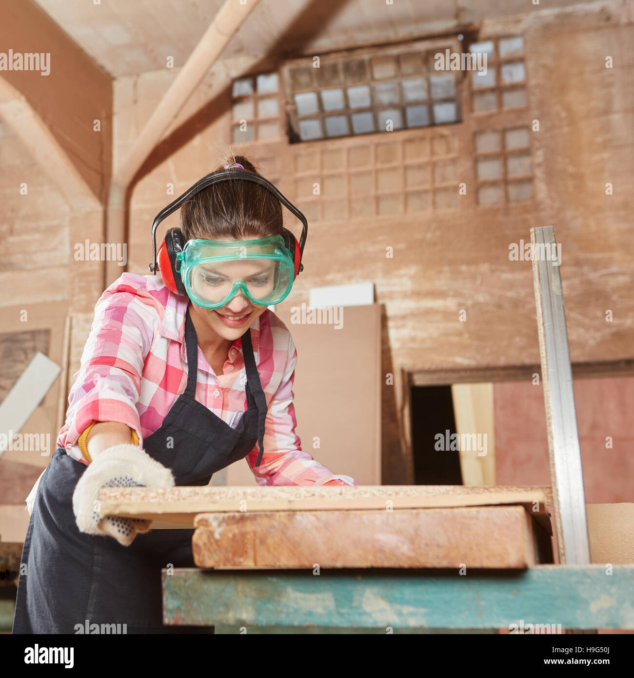 Woman cutting wood with grinder during her apprenticeship - Stock Image