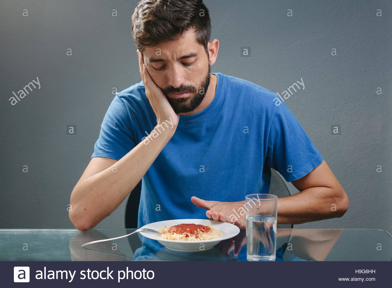 Portrait of man with no appetite in front of the meal. Concept of loss of appetite - Stock Image