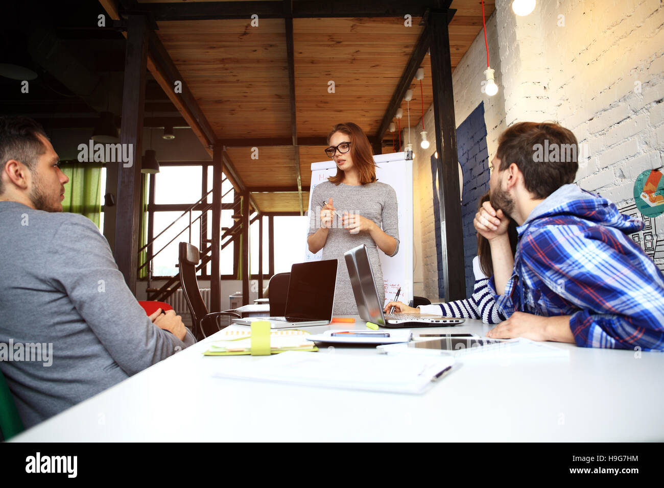Team members listening attentively to a cheerful business woman holding a presentation. - Stock Image