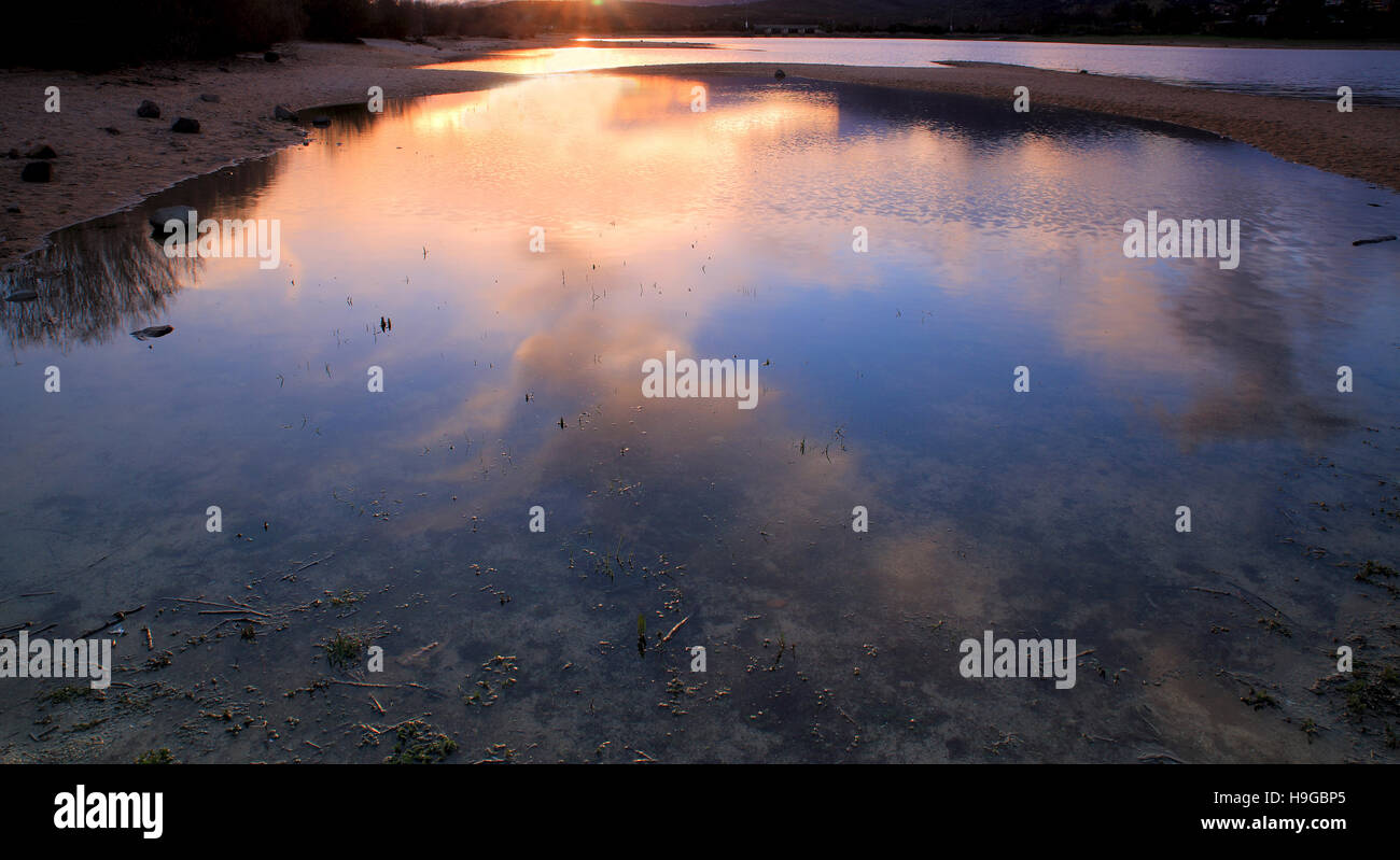 Reflections of the sun at sunset on the water of a lake - Stock Image
