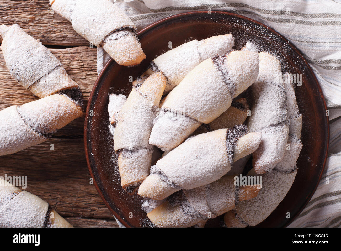 crescent rolls with poppy seeds macro on a plate on the table. horizontal view from above - Stock Image