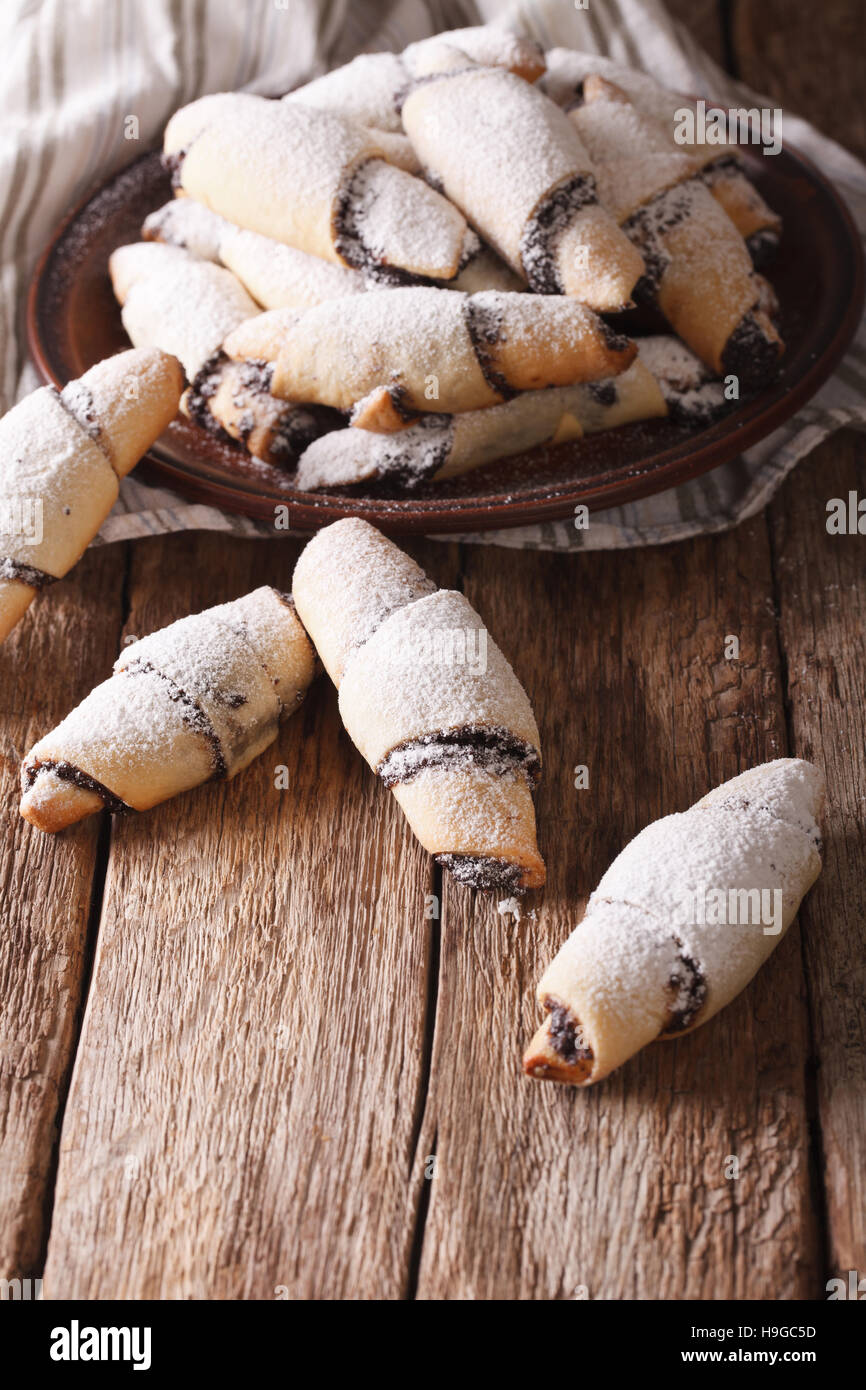 Freshly baked crescent with poppy stuffing close-up on a plate on the table. vertical - Stock Image