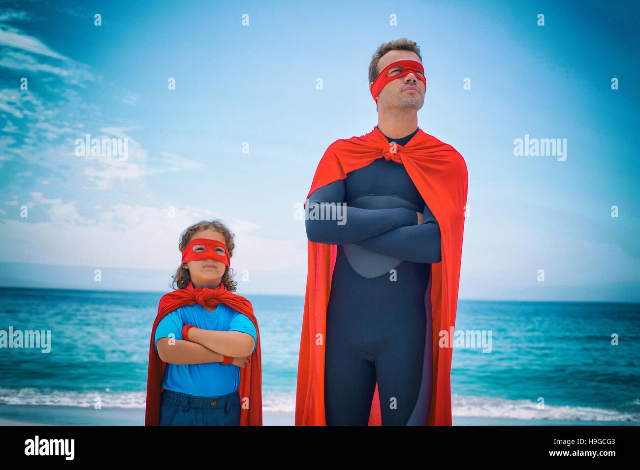 Confident man and son standing at sea shore - Stock Image