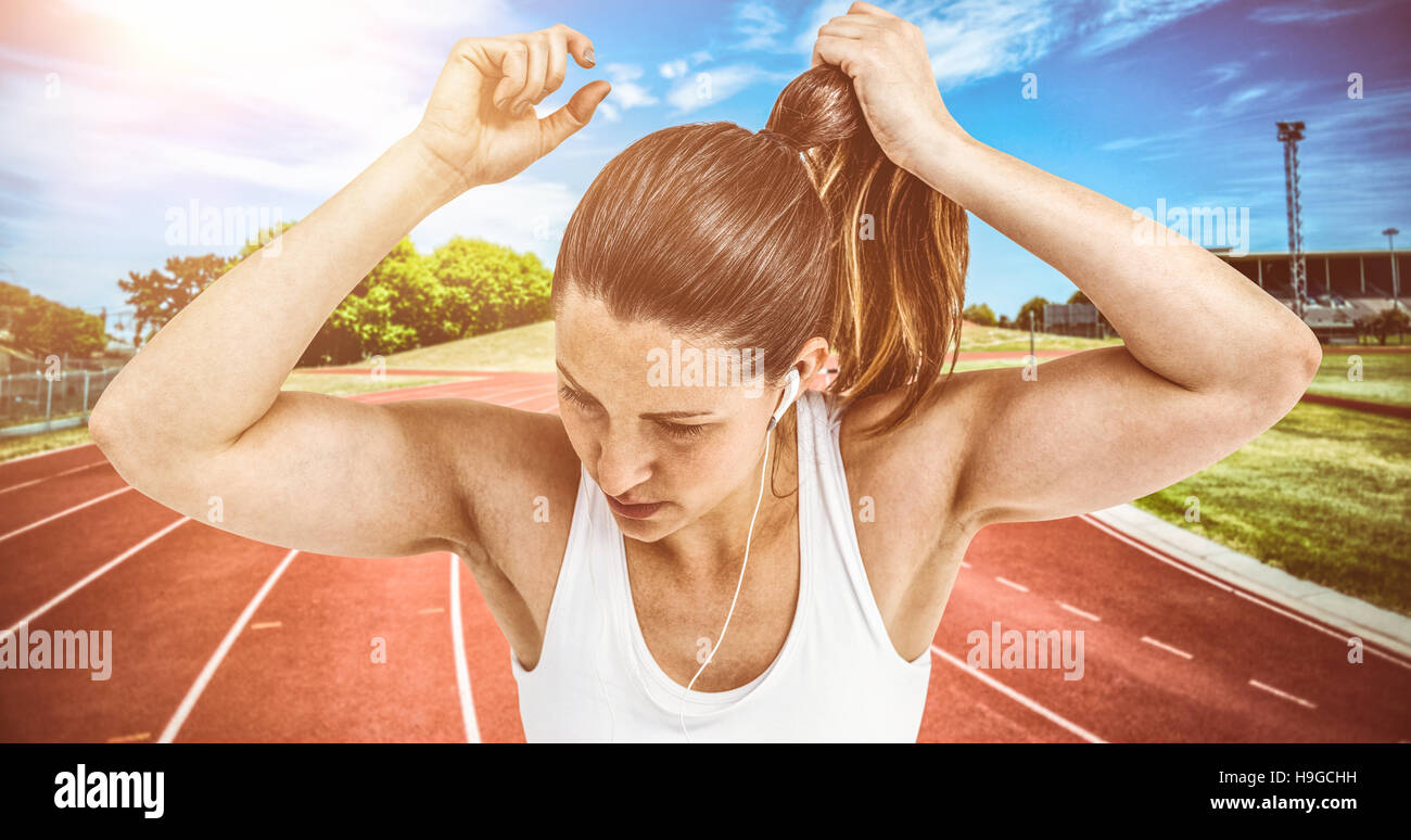 Composite image of athlete woman tying her hair and listening to music - Stock Image