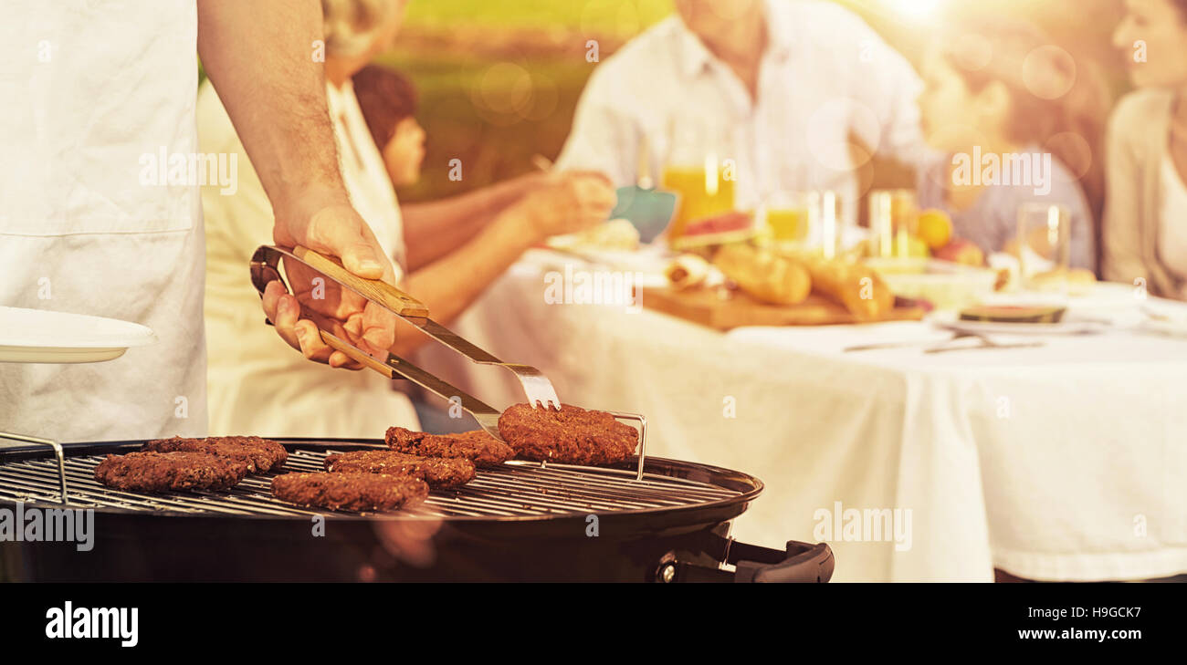 Barbecue grill with extended family having lunch in park - Stock Image