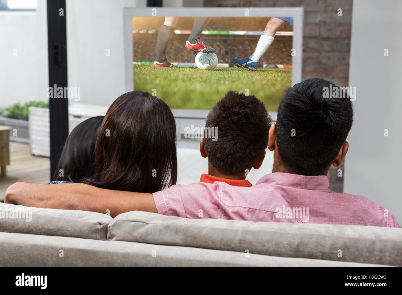 Composite image of happy family watching tv on the sofa - Stock Image