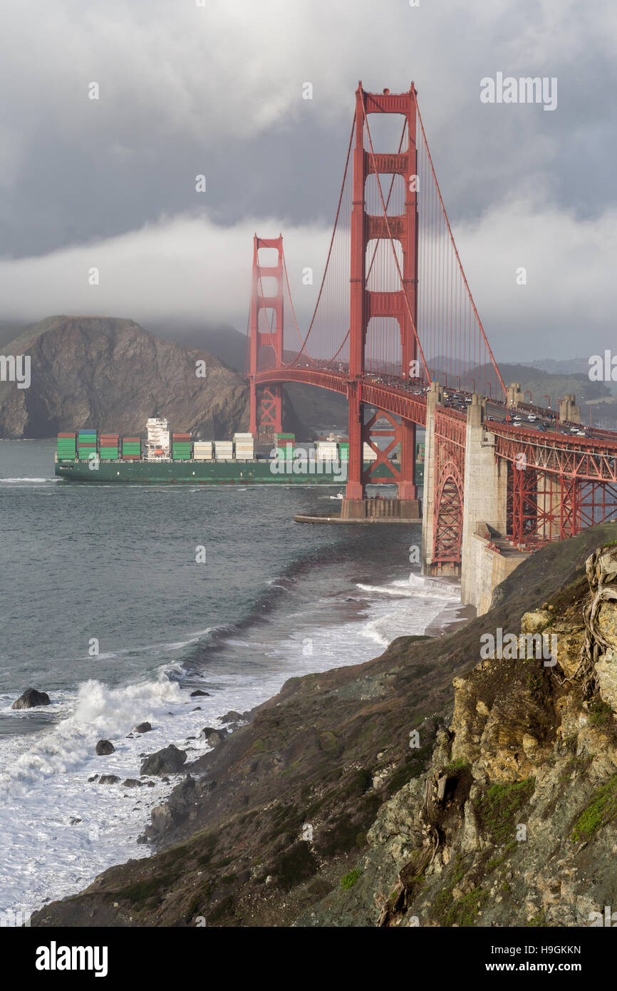 Cargo ship crossing the Golden Gate Bridge during a storm. - Stock Image