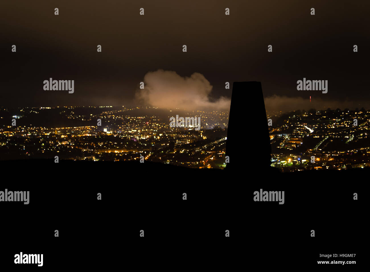 Silhouetted trig point on Little Solsbury Hill. Night view of City of Bath, with stone for cartographic triangulation - Stock Image
