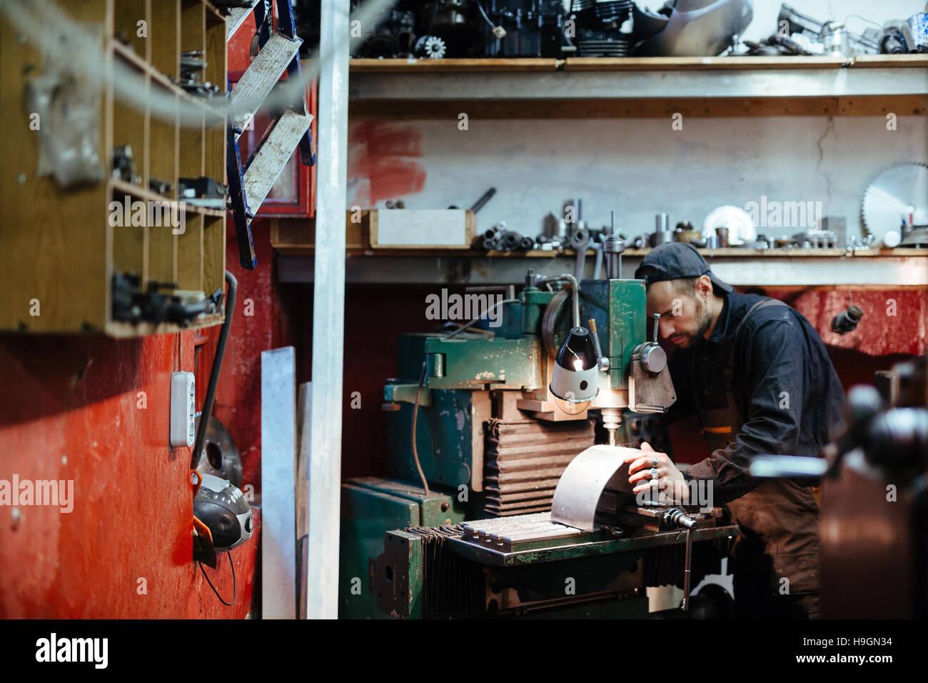 Workman drilling or grinding metallic sheet - Stock Image
