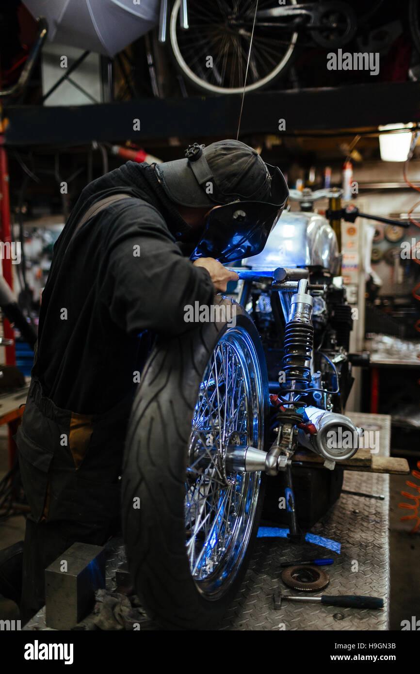 Professional custom-bike repairman welding metallic details of bicycle in workshop - Stock Image