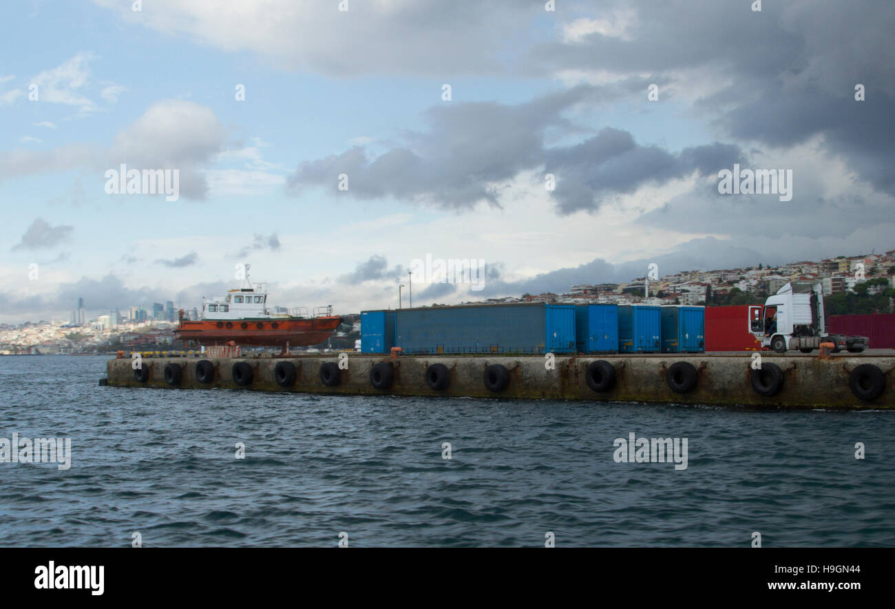 Seaport containers warehouse near sea and storm sky and old ship - Stock Image