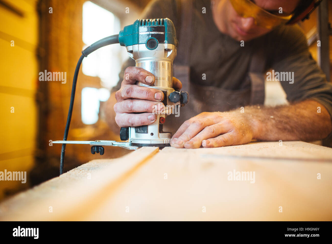 Skilled handyman cutting wooden board with electric wood-router - Stock Image