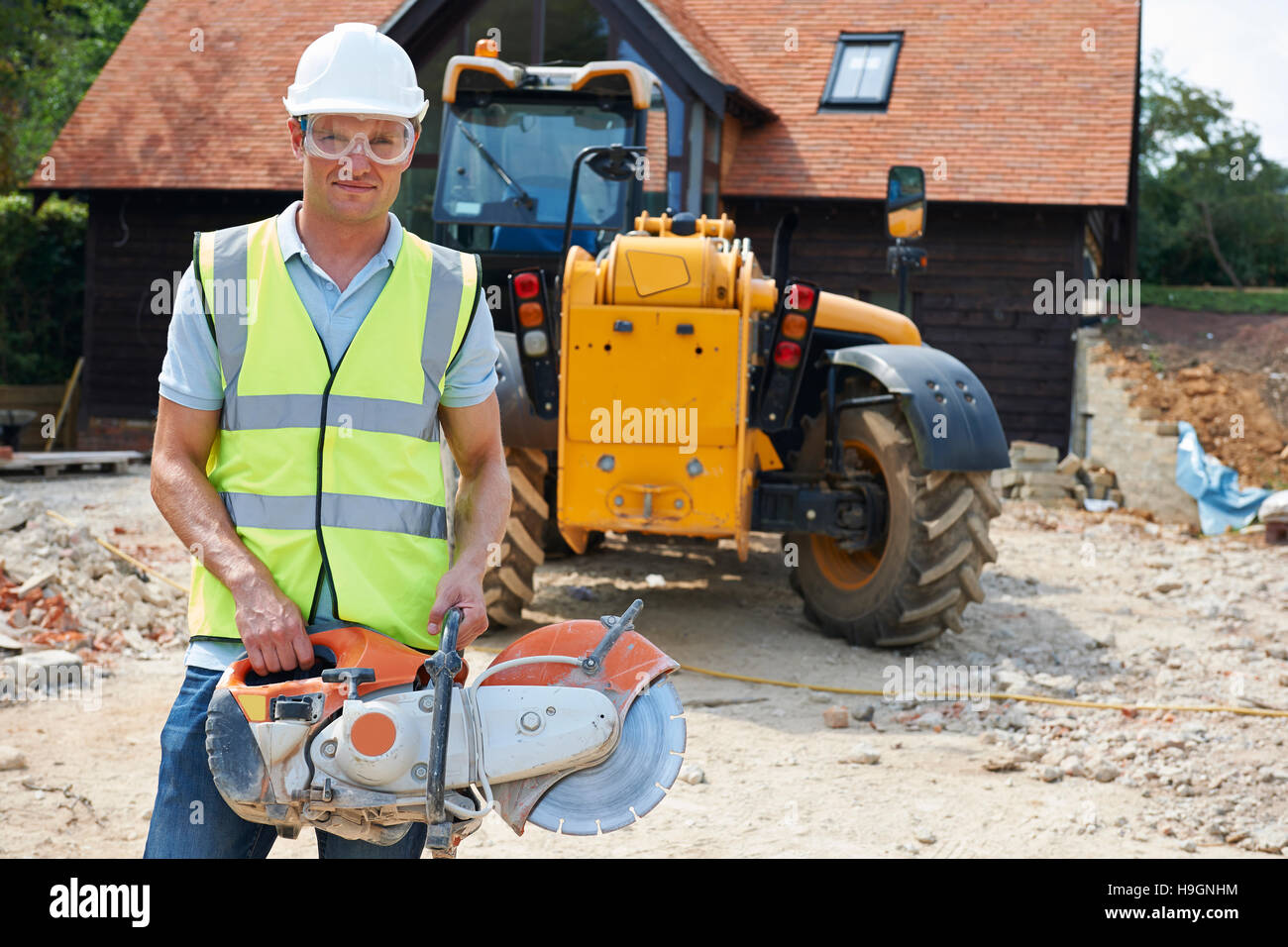 Construction Worker On Site Holding Circular Saw - Stock Image