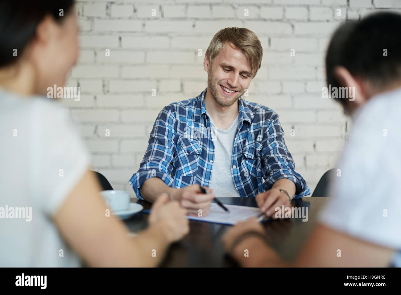 Young candidate for vacancy asking questions of employers - Stock Image