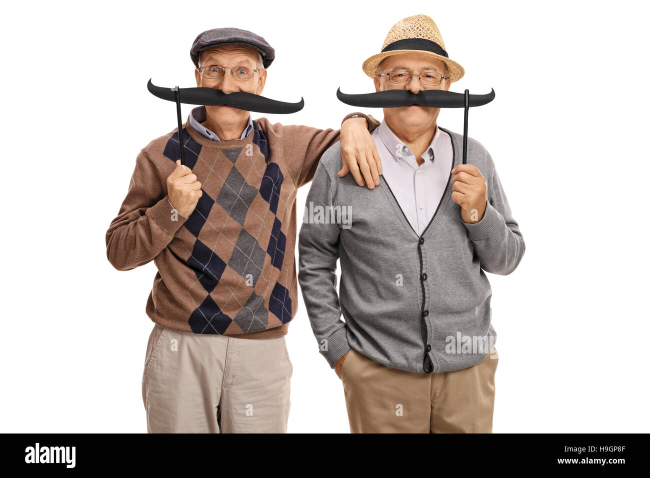 Seniors posing with big fake moustaches isolated on white background - Stock Image