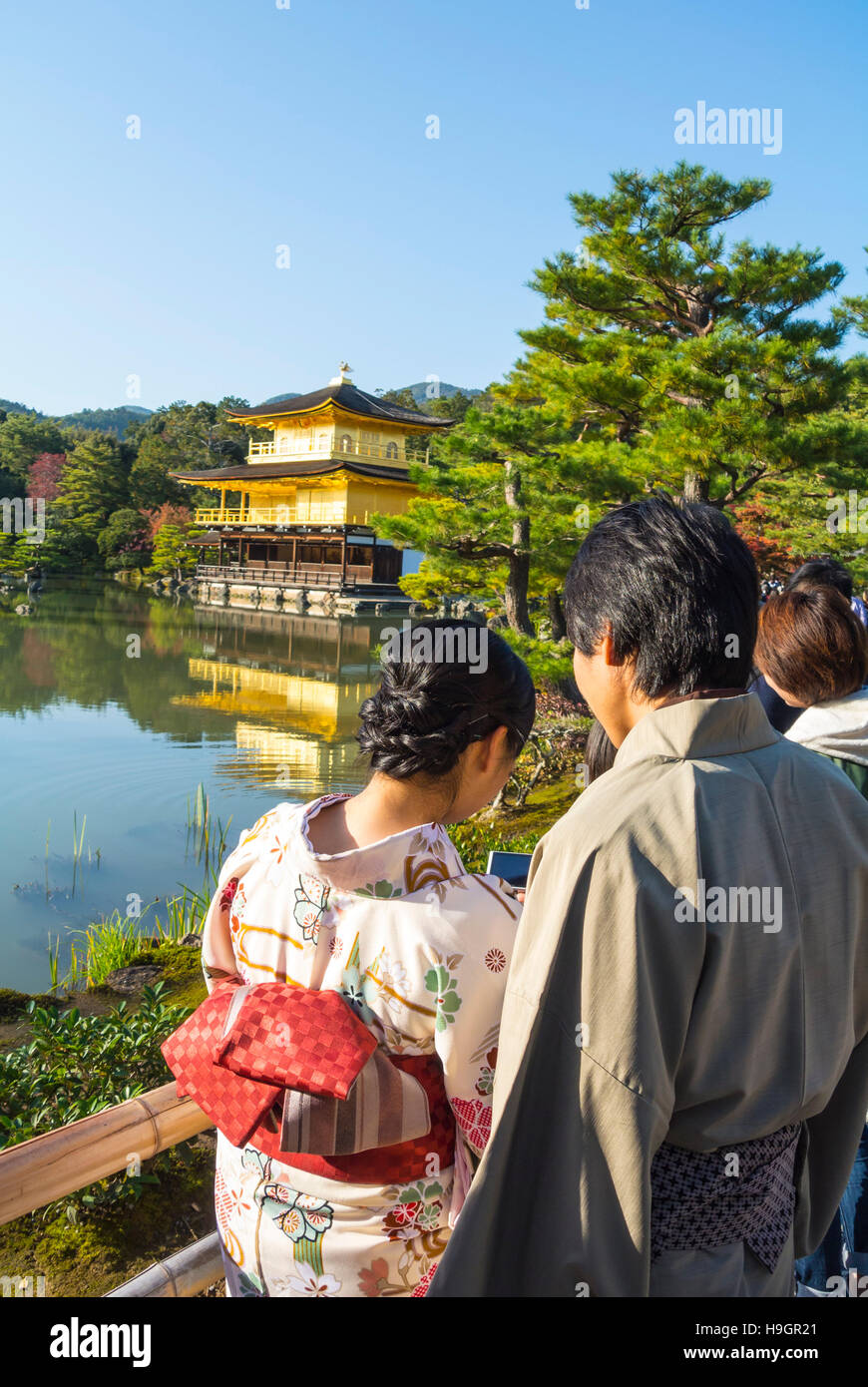 japanese couple by temple of the golden pavilion, Kyoto, Japan - Stock Image