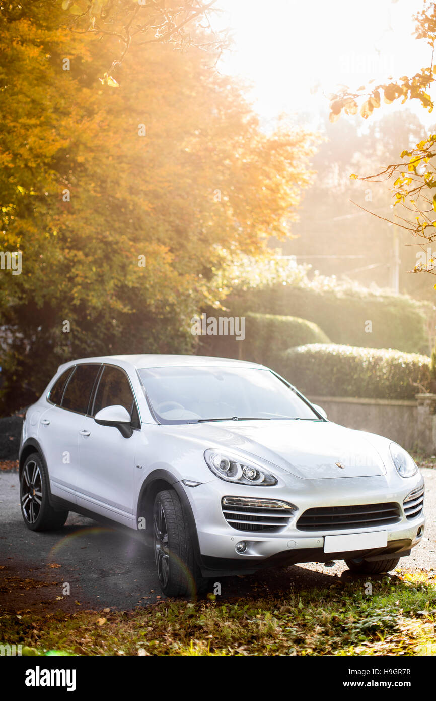 UK European Porsche Cayenne in silver in a car park in the autumn sun. - Stock Image