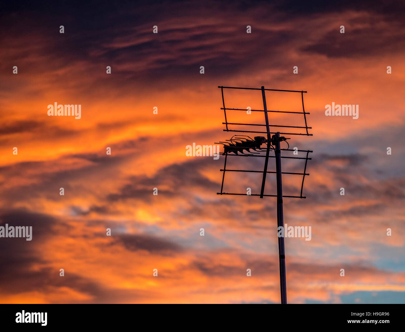 Silhouette of TV aerial against dramatic sunset - Stock Image