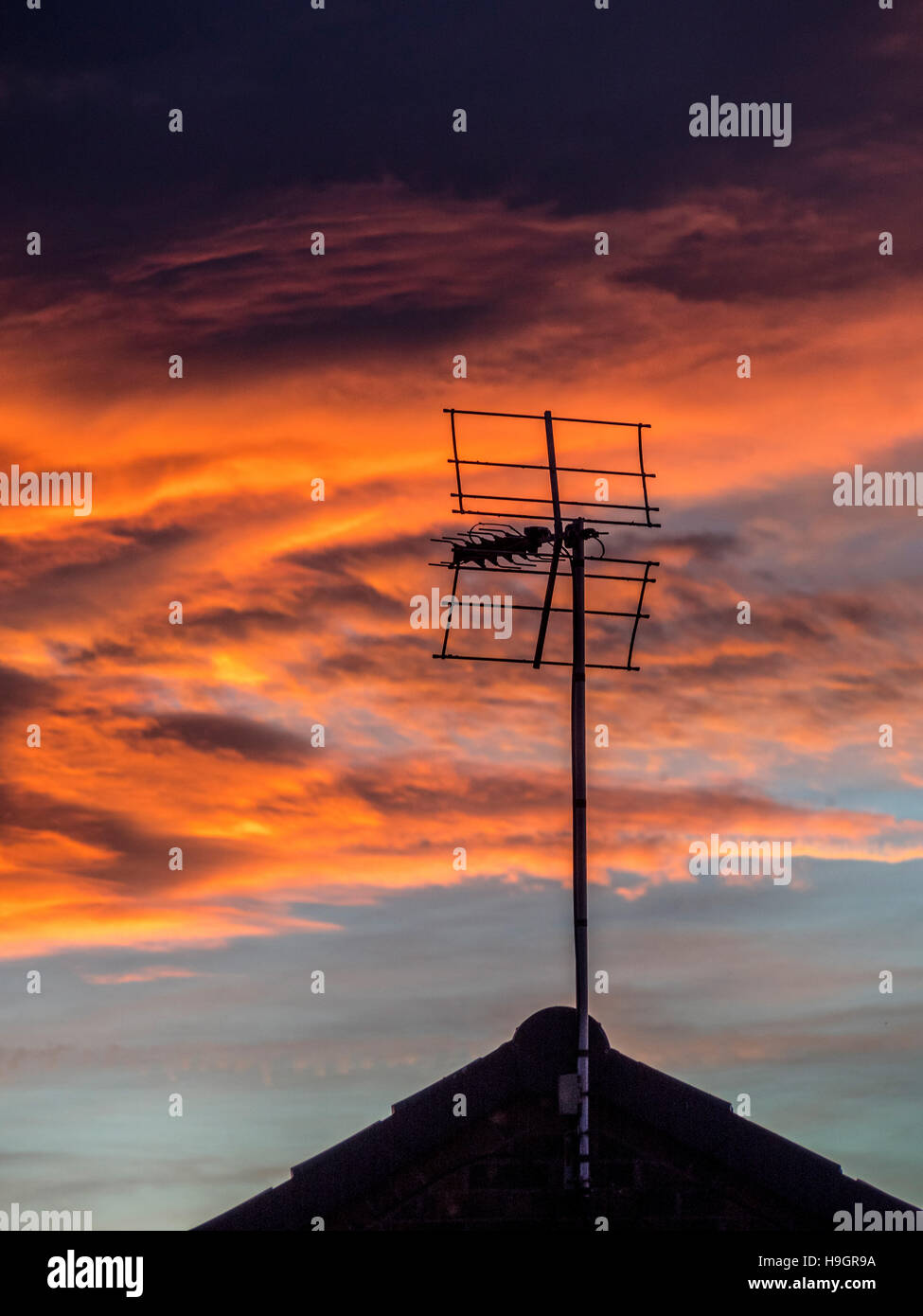 Silhouette of TV aerial and house roof against dramatic sunset - Stock Image