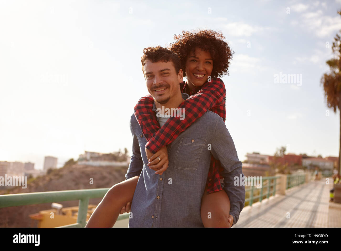 Joyful young girl getting a piggy back as she smiles a toothy smile with her arms around his neck while looking - Stock Image