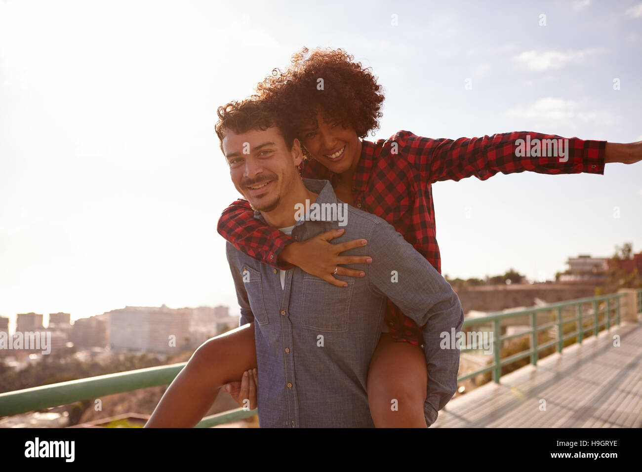 Playful young couple playing aeroplane her left arm out and holding onto his chest with her right arm while getting - Stock Image
