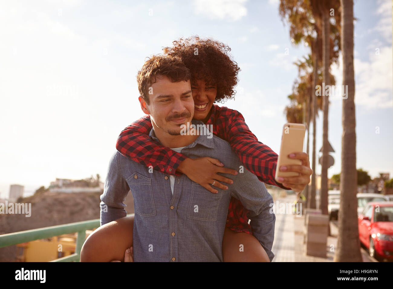 Piggy back riding girl taking a selfie of them while sitting on her boyfriends back holding on with her right hand - Stock Image