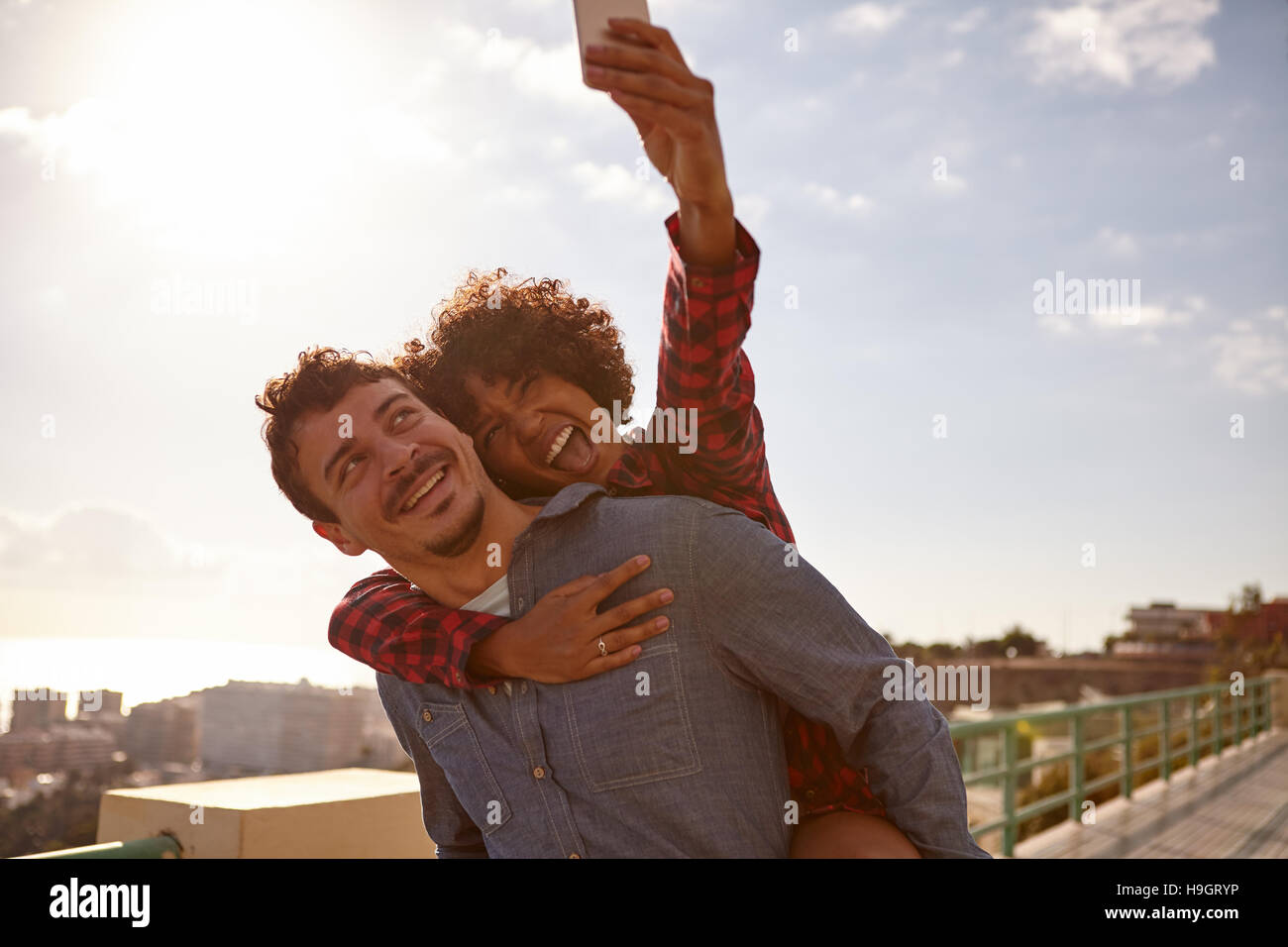 Piggy back riding girl with open mouth, taking a selfie of them while sitting on her boyfriend back holding on with - Stock Image
