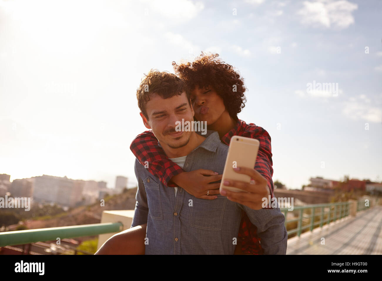 Kiss blowing, piggy back riding girl taking a selfie of them while sitting on her boyfriend back holding on with - Stock Image
