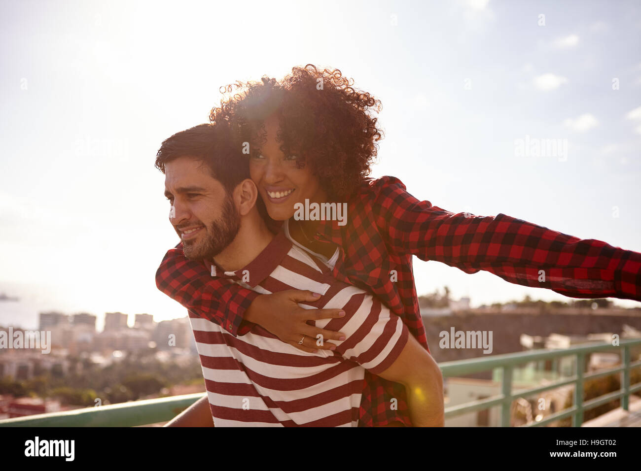 Playful loving couple gesturing aeroplane with her left arm out and holding onto him with her right arm while getting - Stock Image