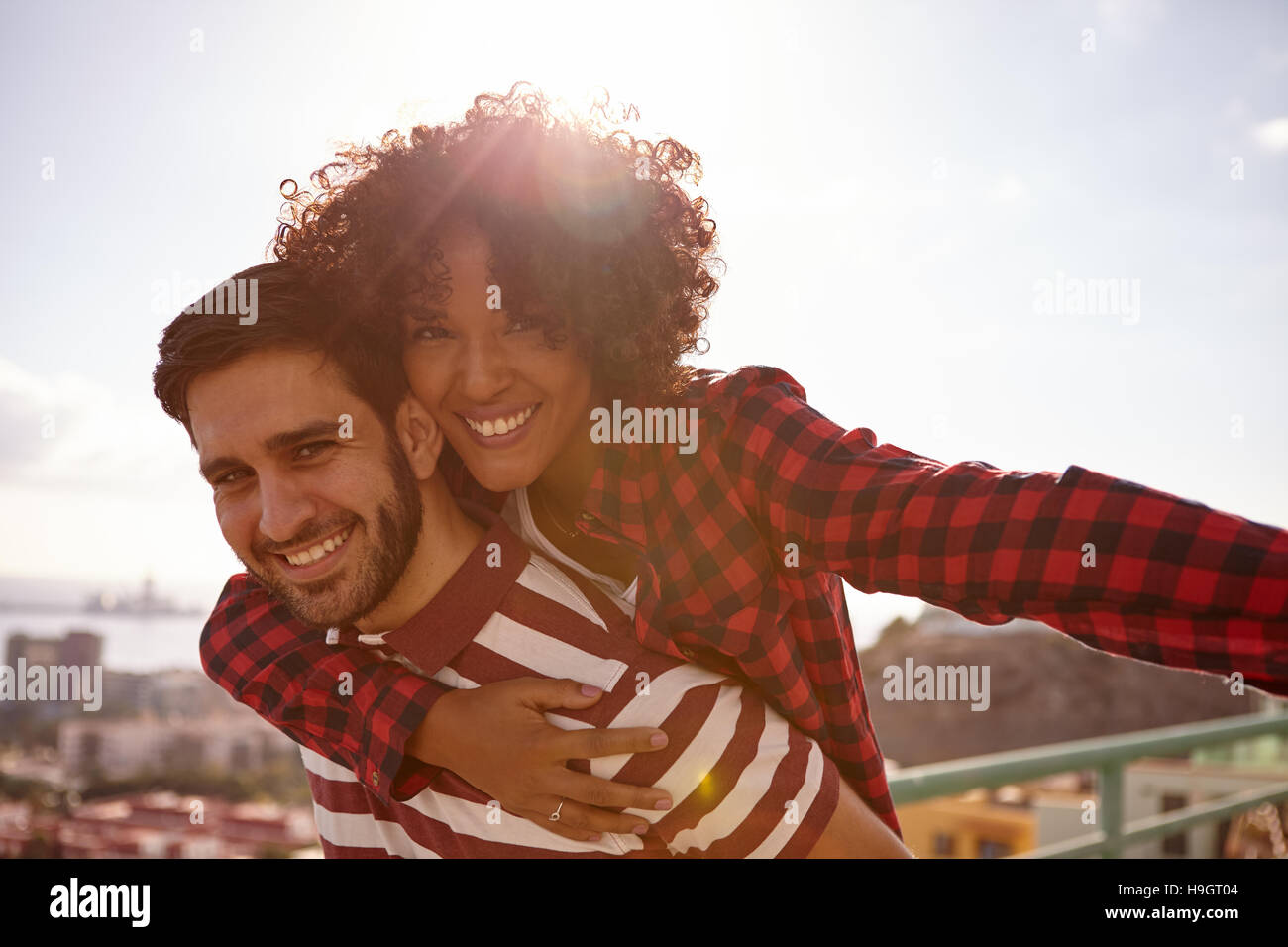 Loving couple gesturing aeroplane with her left arm out and holding onto him with her right arm while getting a - Stock Image