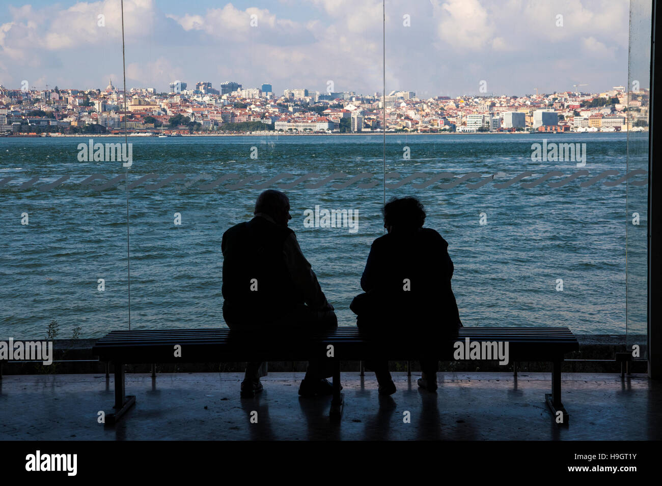 Lisbon. Pensioner couple waiting at Almada ferry terminal  on the south side of the river making Lisbon easily accessible - Stock Image