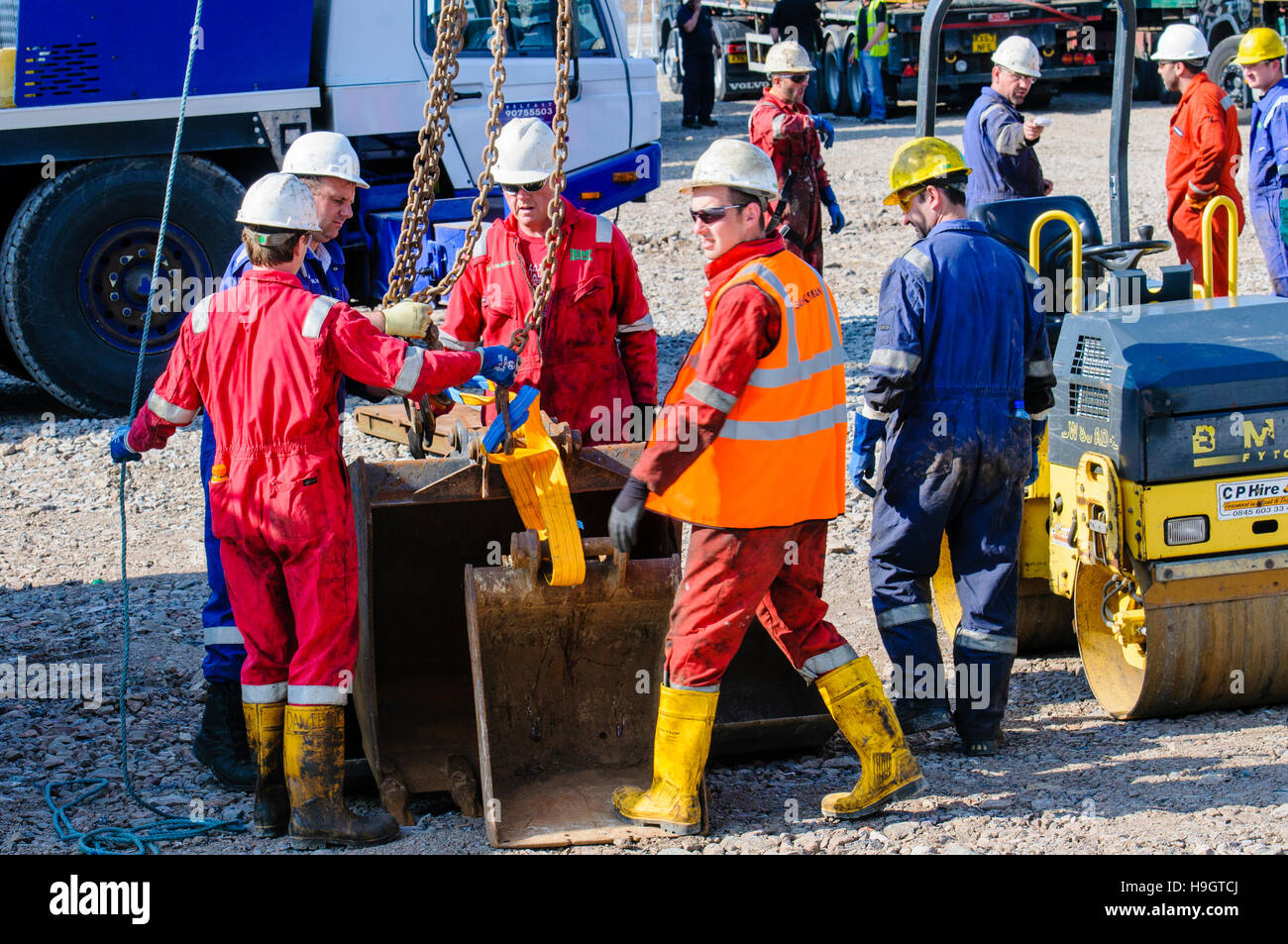 Construction workers prepare a crane hook to lift backhoe digger buckets.at an exploratory oil well. - Stock Image