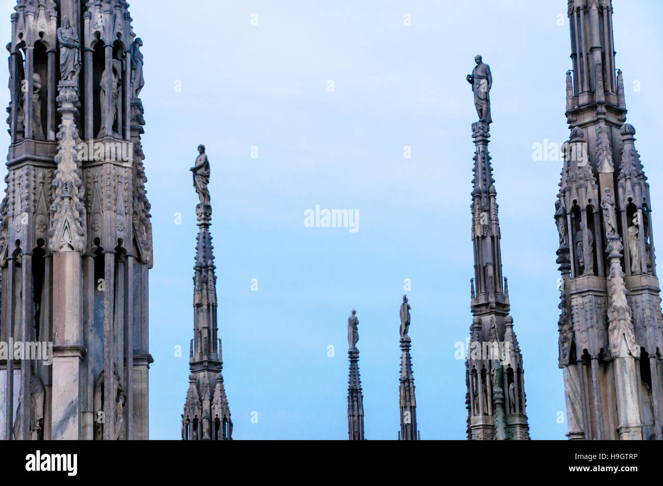 Spires with ornately carved stonework on the roof of the Duomo Milano (Milan Cathedral), Italy - Stock Image