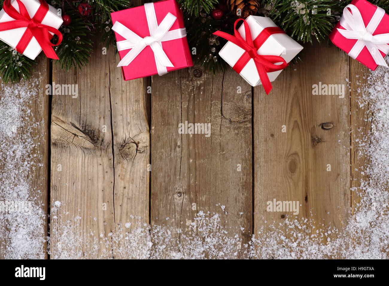 Red And White Christmas Gift Top Border With Branches Snow Frame On A Rustic Wood Background