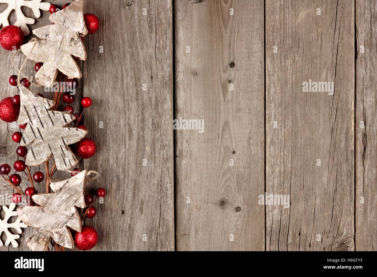 rustic christmas side border with wood ornaments and berries on an aged wood background stock - Rustic Christmas Background