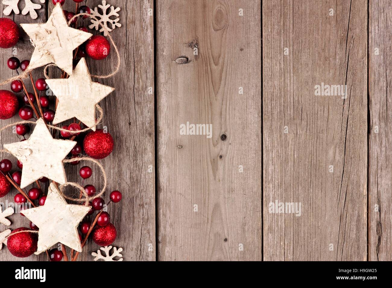 rustic christmas side border with wood star ornaments and baubles on an aged wood background - Rustic Christmas Background