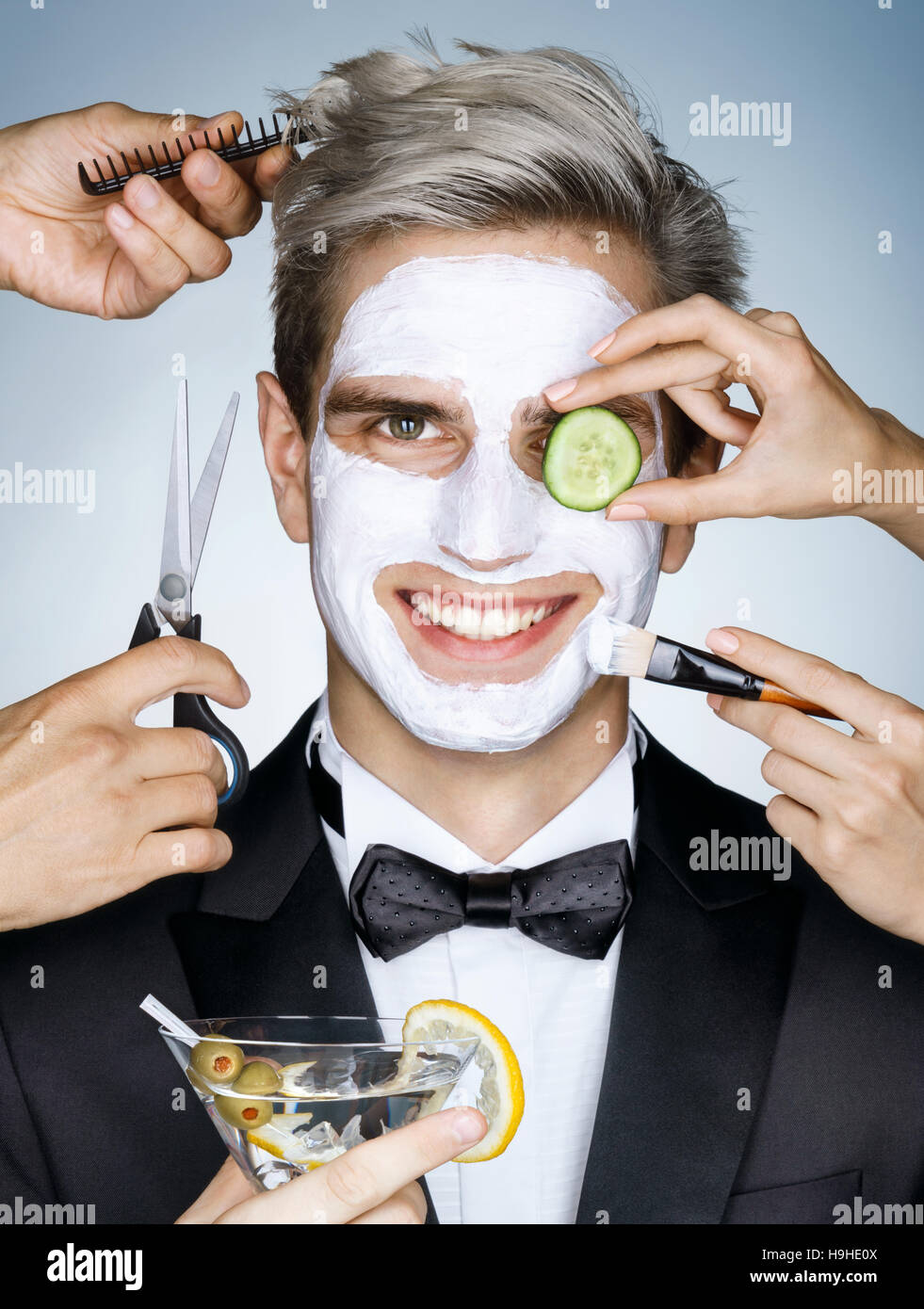 Happy elegant man with moisturizing facial mask surrounded by the multifunctional service  (stylist, beautician, - Stock Image