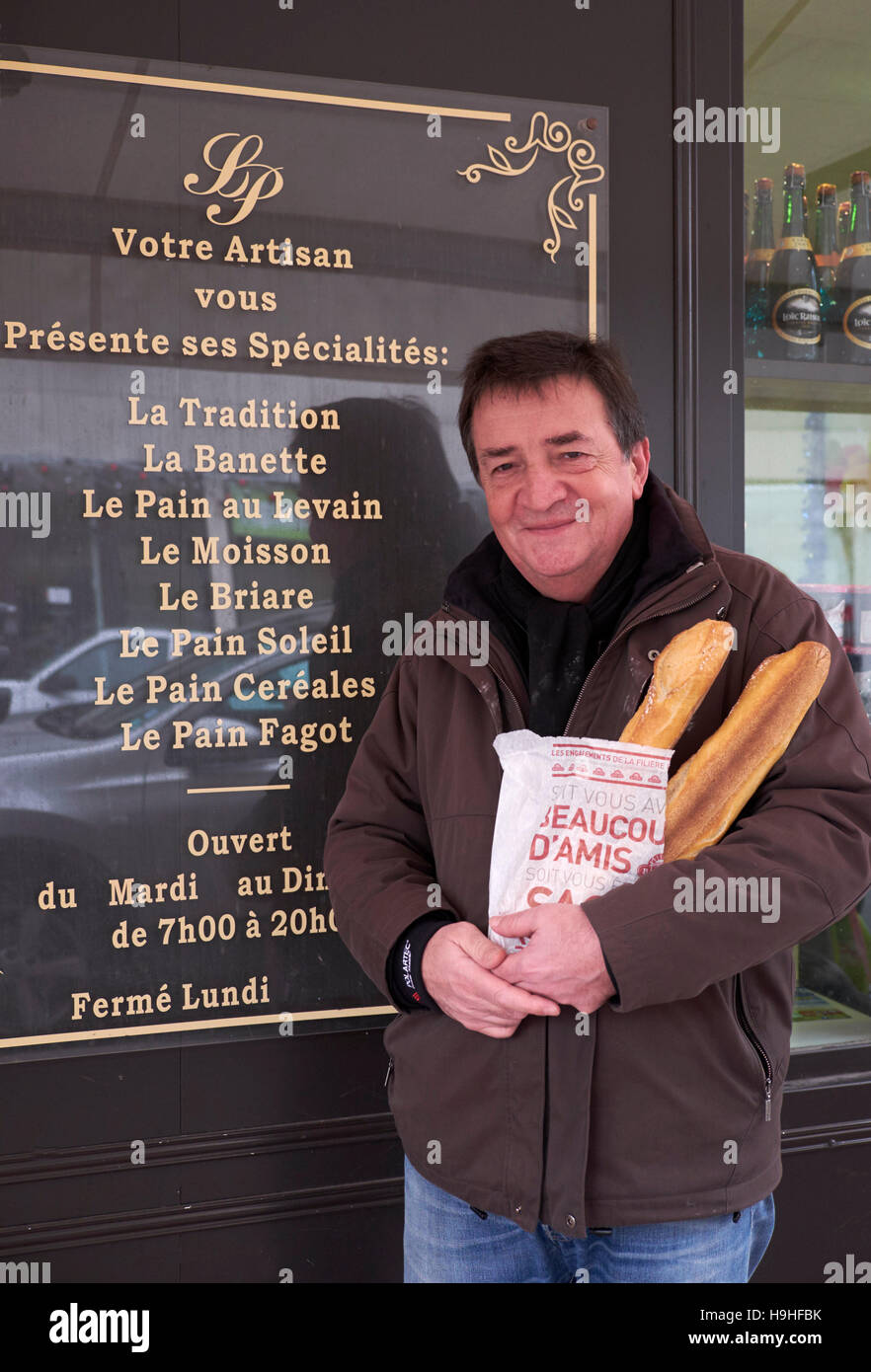 Man standing outside a Boulangerie with two baguettes that he has bought on Christmas Day. Le Perreux-sur-Marne, - Stock Image