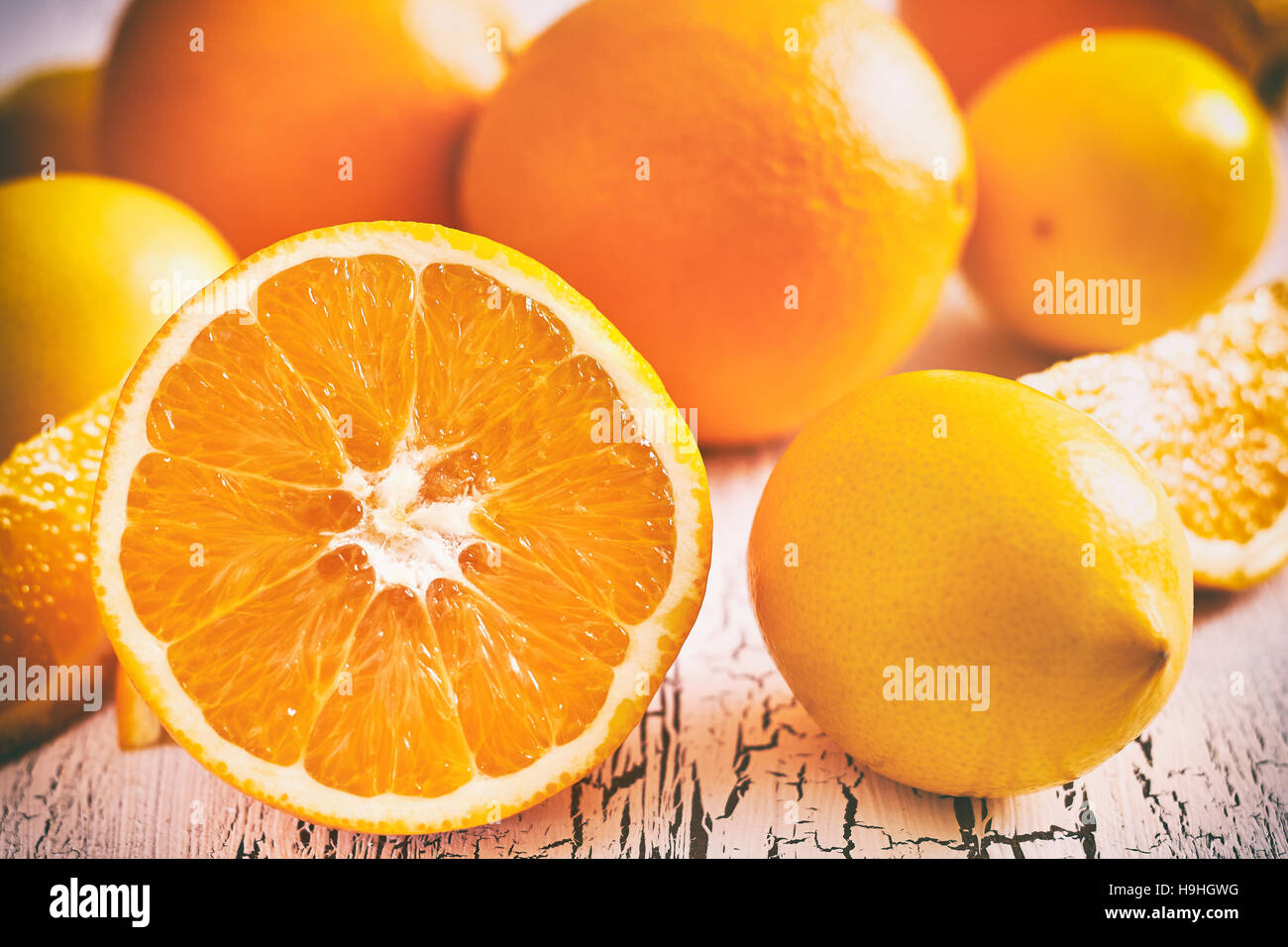 Oranges and lemons on white rustic wooden background - Stock Image