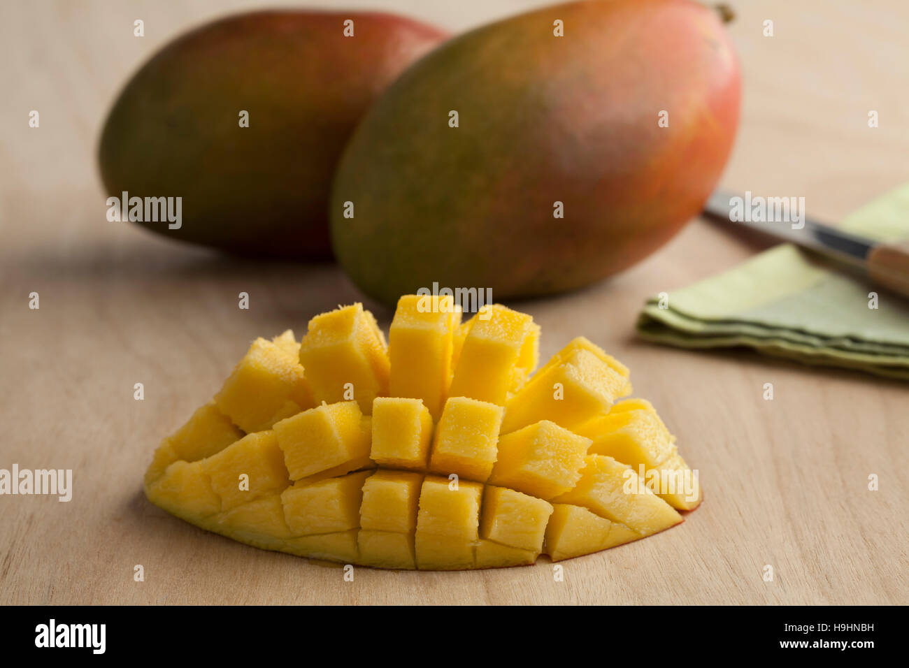 Fresh ripe juicy half yellow mango and whole in the background - Stock Image