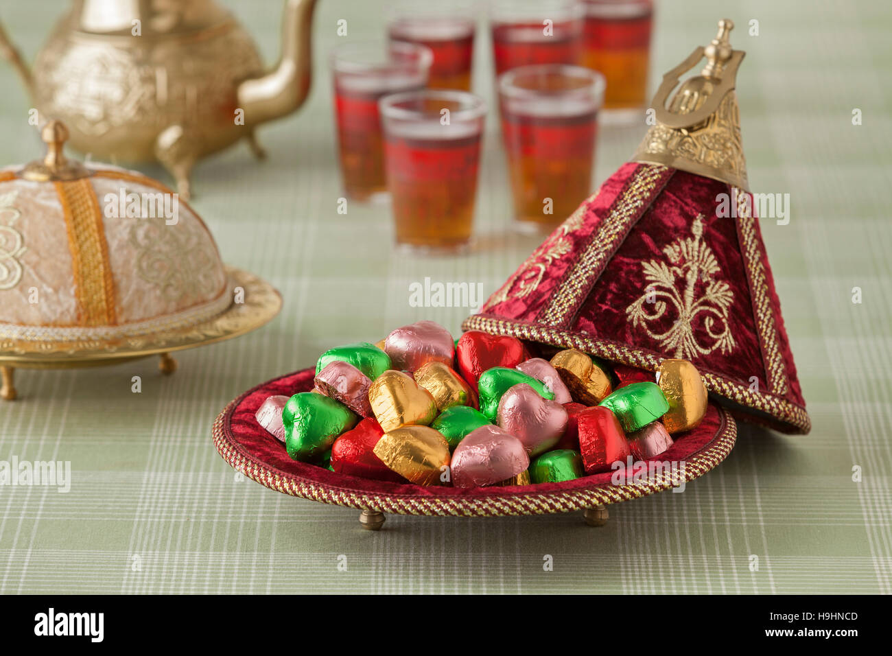 Moroccan festive sweets in a red tajine and tea - Stock Image