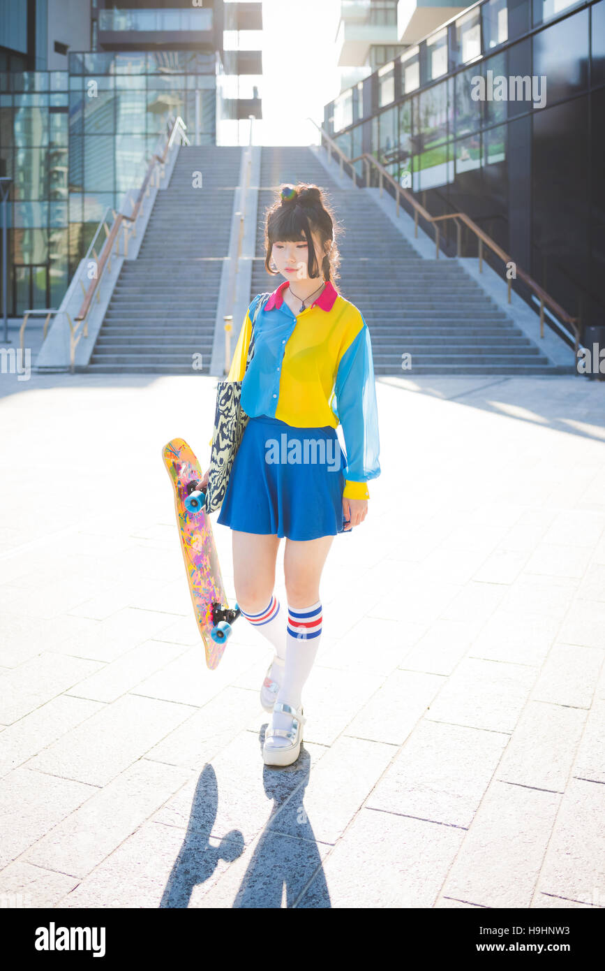 young beautiful asian millennial woman nonconformist skater walking outdoor in the city holding skateboard - eccentric sportive concept & young beautiful asian millennial woman nonconformist skater walking ...