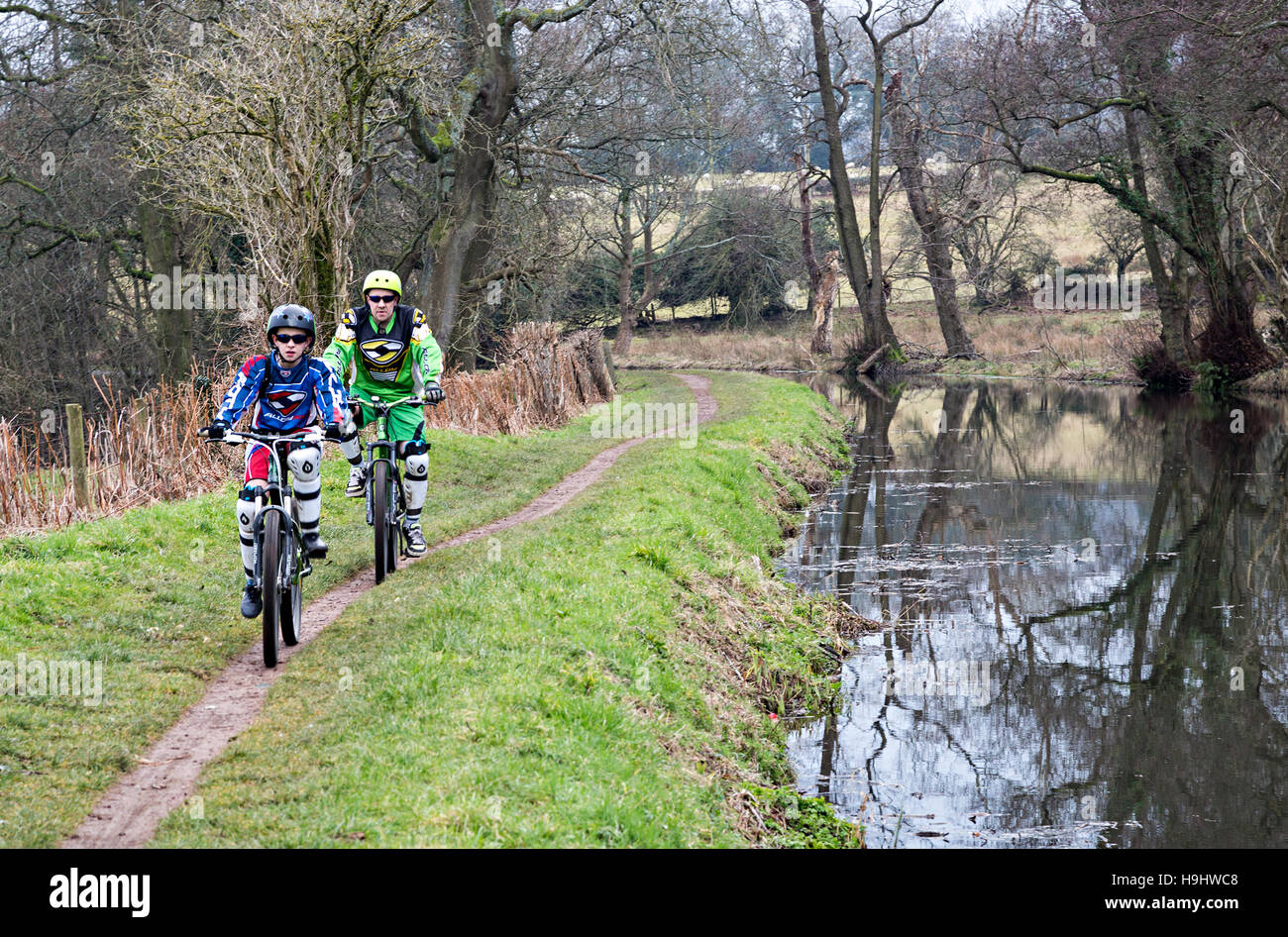 Man and boy cycling on canal towpath, Brecon and Abergavenny Canal, Wales, UK - Stock Image