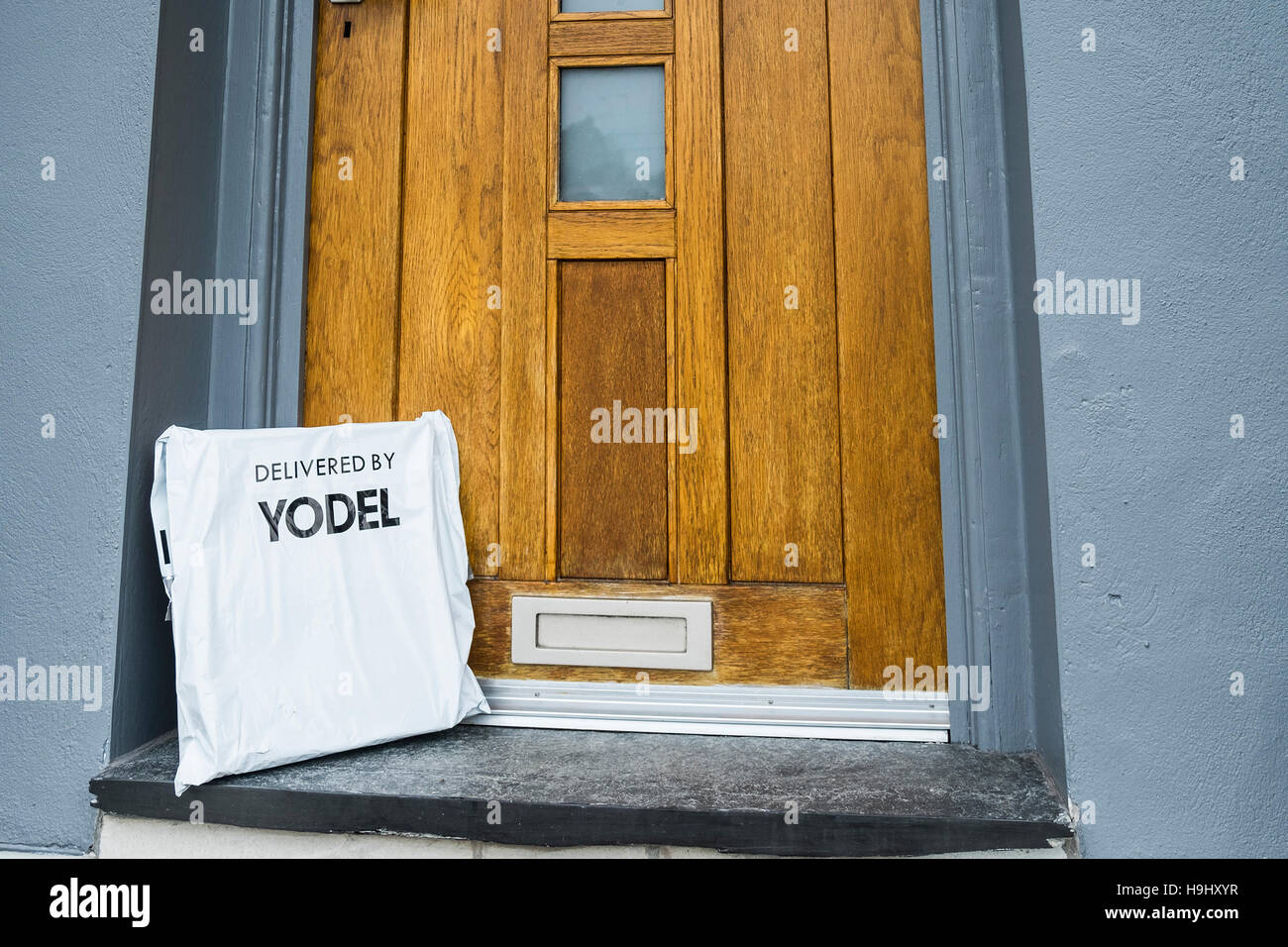 A parcel delivered to a house by Yodel and left on the doorstep. - Stock Image