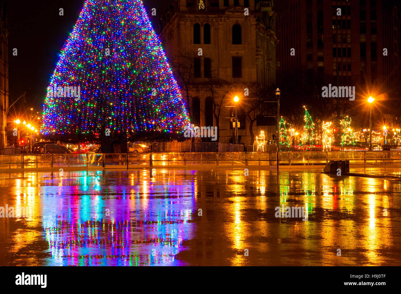 The big lighted Christmas tree in Syracuse NY reflected in the wet skating rink on Clinton Square - Stock Image