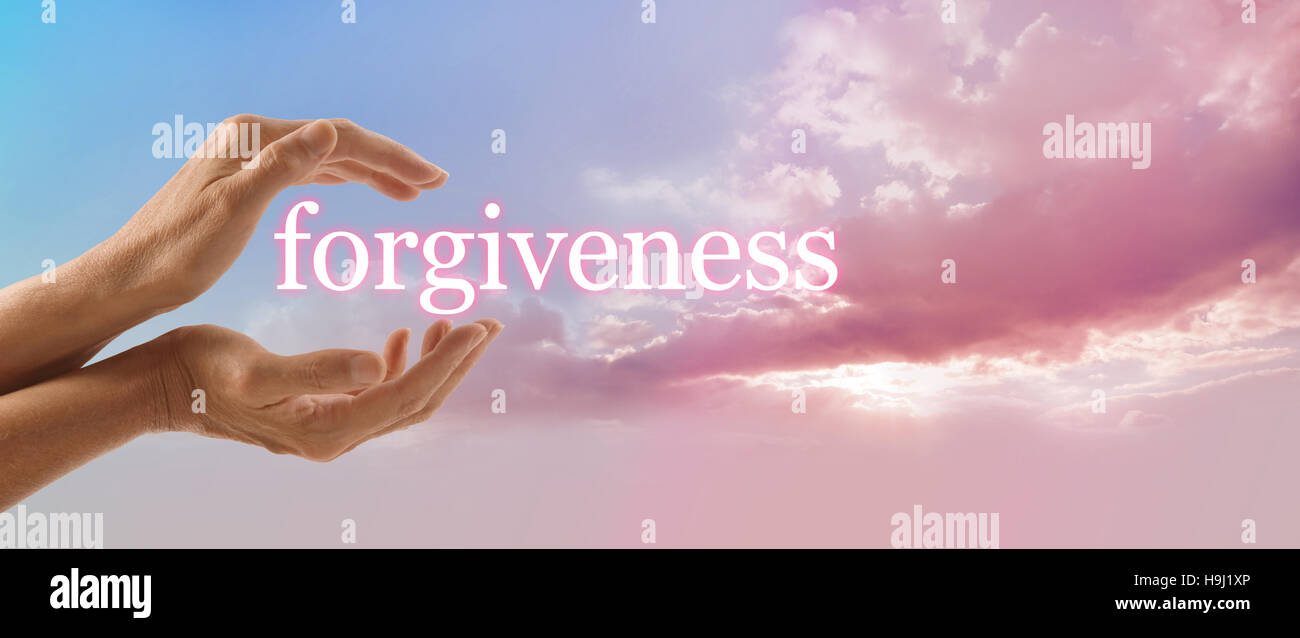 Female hands cupped around the word FORGIVENESS on a blue sky background with a fluffy pink cloud stream and sun - Stock Image