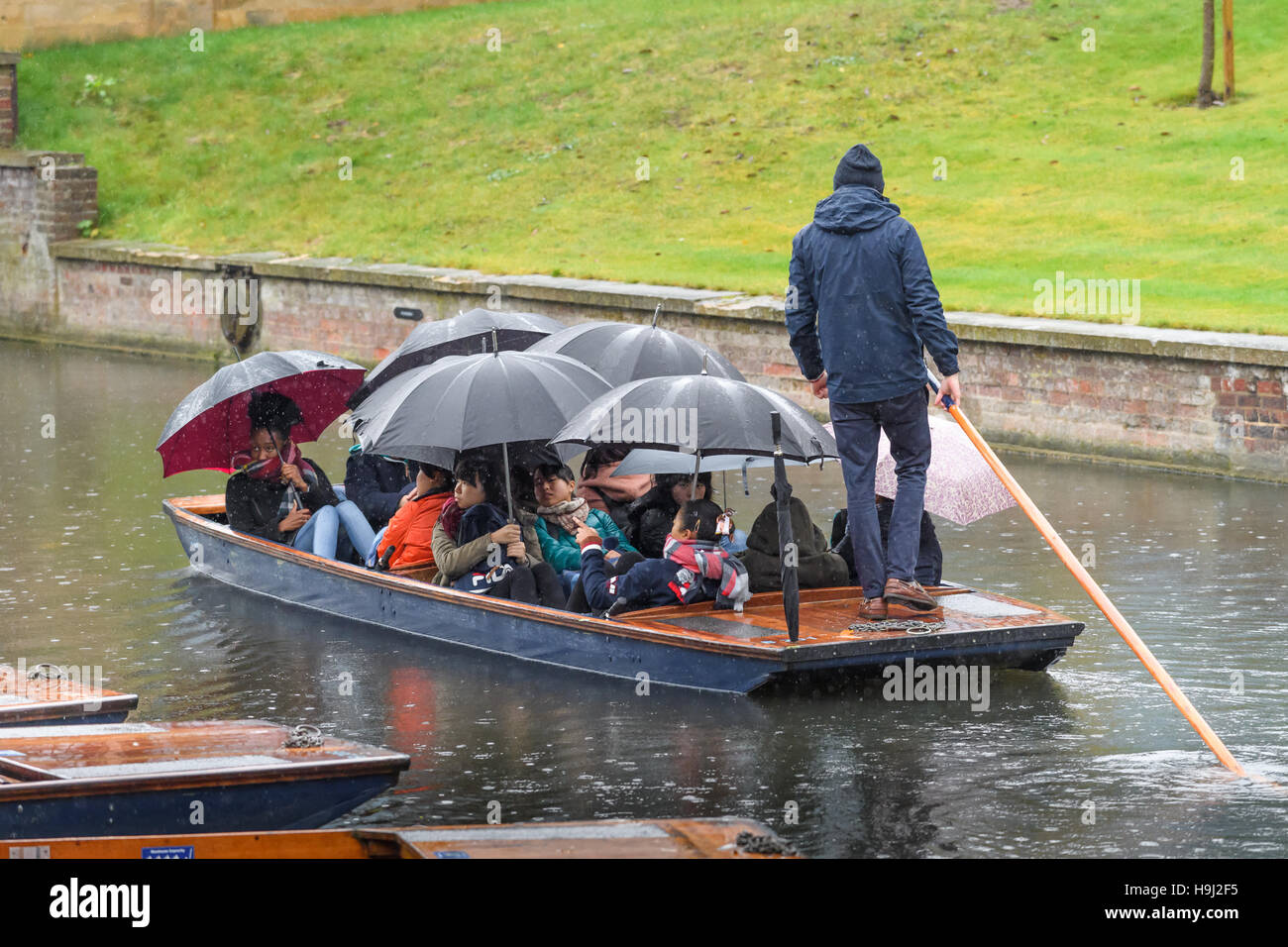 Tourists take a trip in a punt along the river Cam on a rainy day in Cambridge, England. - Stock Image